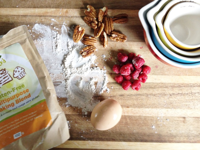 Gluten Free Muffin Flour, egg, walnuts, raspberries and measuring cups on wooden counter