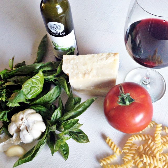 basil leaves, garlic clove, rotini pasta, parmesan cheese wedge, tomato and red wine on white counter
