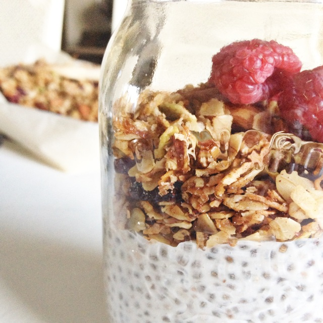 Coconut chia seed pudding topped with granola and raspberries