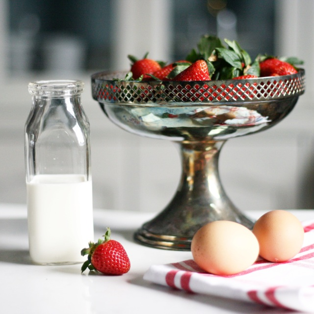 Bowl of strawberries, glass jug of milk and two eggs on white counter