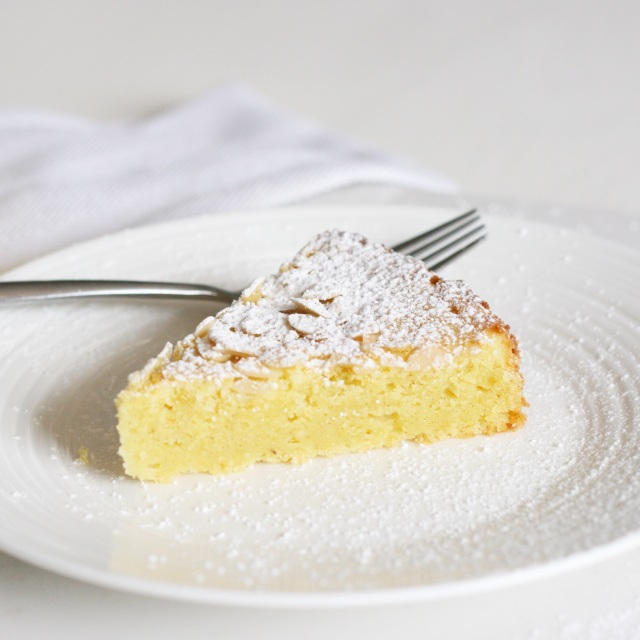 Slice of lemon almond ricotta cake on white plate