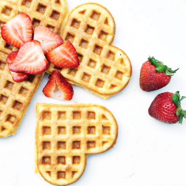 Heart shaped buttermilk waffles topped with strawberries