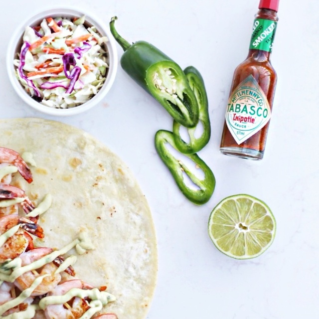Prawn tacos with avocado crema, jalepeno peppers and hot sauce